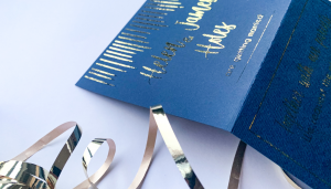 a navy blue section of a wedding invitation with gold foiled writing and gold ribbon