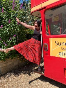 Sally the celebrant in a fun and happy pose on a wedding bus